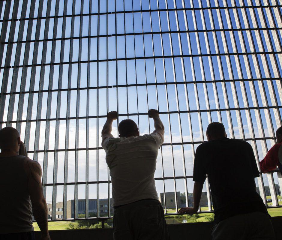 Billede af indsatte bag hegnet i Enner Mark Fængsel