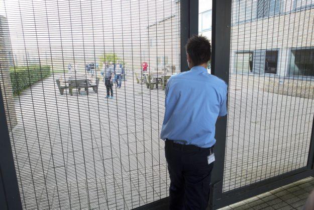 Billede af fængselsbetjent, der låser en port.