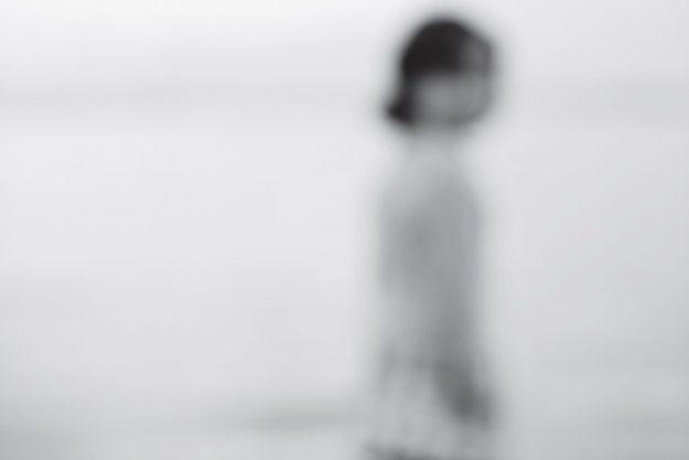 Sløret sort-hvidt billede af et barn