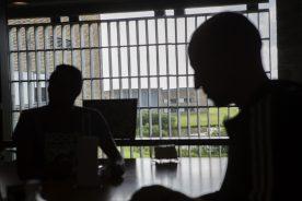Silhuetter af indsatte der sidder bag et cellevindue i Enner Mark. Den ene sidder bag ved en computerskærm.