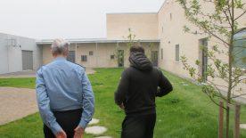 En fængselsbetjent og en indsat med en sort dunjakke på, går en tur i gården i Enner Mark Fængsel.