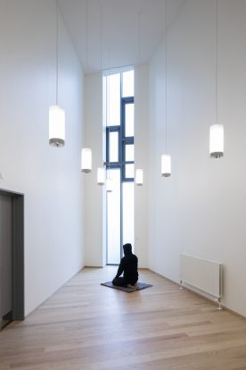 En indsat sidder i bedestilling i bederummet i Storstrøm Fængsel.