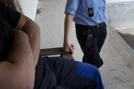 En indsat sidder med korslagtearme på en bænk, mens en fængselsbetjent står ved siden af og hviler sin hånd på bænken.