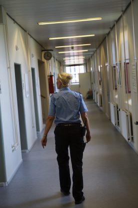 En fængselsbetjent bagfra der går ned af en cellegang i raskt tempo.