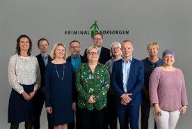 Kriminalforsorgens koncernledelse, bestående af 10 personer. Alle står placeret foran kriminalforsorgens logo.