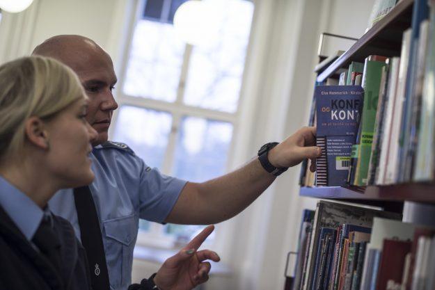 To fængselsbetjentelever i uddannelsescenteret i Birkerøds bibliotek. Den ene elev tager en bog ned fra reolen, som den anden peger på.