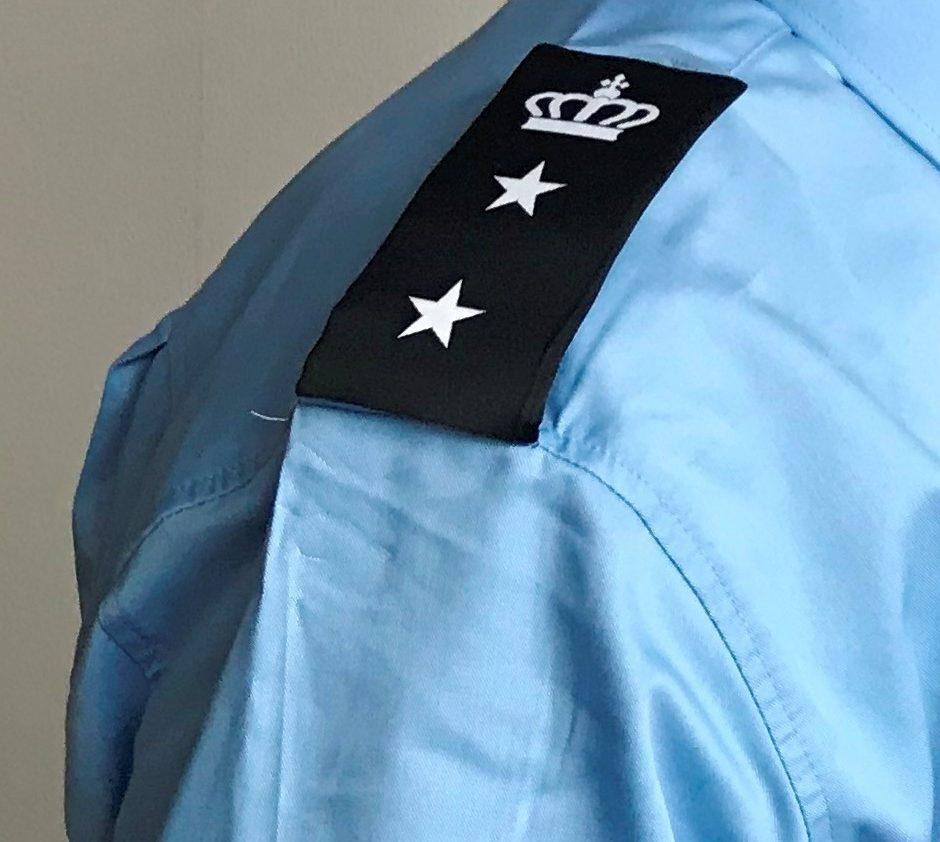 Billede af fængselsbetjents skulder, så man kan se distinktioner og etatsmærke på uniformen